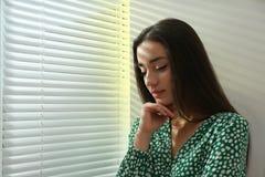 在窗口附近的年轻女人与软百叶帘 库存照片