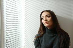 在窗口附近的年轻女人与软百叶帘 免版税库存图片