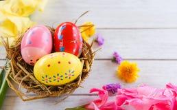 在篮子巢装饰的复活节彩蛋与五颜六色的剑兰花春天夏天 库存照片