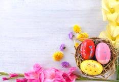 在篮子巢装饰的复活节彩蛋与在白色背景的五颜六色的剑兰花 库存图片