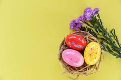 在篮子巢装饰的复活节彩蛋与在黄色的紫色延命菊花 图库摄影