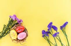 在篮子巢装饰的复活节彩蛋与在黄色背景的紫色花延命菊和statice花 库存照片