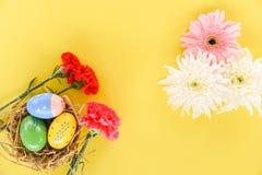 在篮子巢装饰的复活节彩蛋与红色康乃馨花春天夏天和桃红色白色大丁草 库存图片