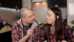 在红色衬衣的愉快的年轻夫妇吃晚餐在桌上 厨房,房子 影视素材