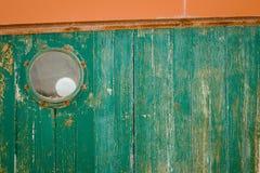 在绿色困厄的木头的圆的窗口 库存图片