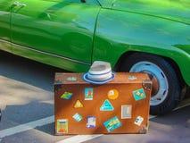 在绿色汽车背景的一个老手提箱 库存照片