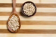 在罐和木匙子的豆罐在竹木背景 图库摄影