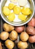 在罐和新鲜的土豆的被剥皮的土豆 免版税库存照片