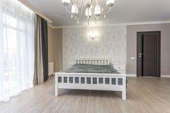 在现代卧室的内部的木床顶楼舱内甲板的在昂贵的公寓 库存图片