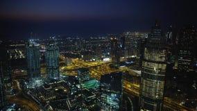 在现代未来派摩天大楼的惊人寄生虫空中全景飞行夜光迪拜都市风景的 股票录像