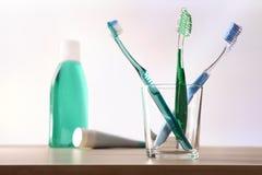在玻璃杯子的牙刷在桌上和牙膏和漱口 图库摄影