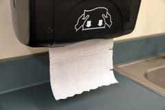 在烘干手的墙壁上的毛巾纸dispensoer在洗手以后清洗他们 免版税库存图片