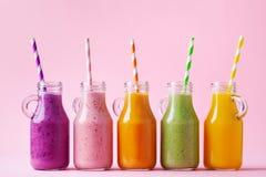 在瓶子的夏天五颜六色的果子圆滑的人在桃红色背景 健康,戒毒所和饮食食物概念 免版税库存照片