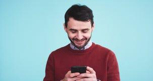 在照相机前面的愉快和微笑的吸引人人使用他的对键入一则消息的智能手机在有a的一个演播室 股票视频