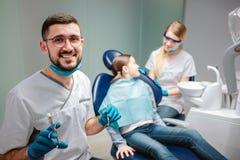 在照相机和微笑的愉快的男性牙医神色 他拿着工具 在女孩的女性牙医立场 孩子在牙齿椅子坐 免版税库存图片