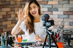 在照相机的微笑的亚裔妇女挥动的手在与化妆用品的桌上 免版税库存照片