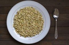 在白色板材的发芽的荞麦有在木桌上的匙子的 免版税库存图片