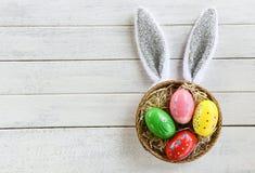 在白色木背景顶视图的五颜六色的复活节彩蛋和复活节兔子耳朵兔子篮子巢装饰 图库摄影