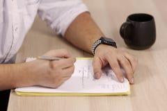 在白色成套装备的人手写与路辗笔在本文在木桌一些拉丁医学术语 在桌上的杯子 免版税图库摄影