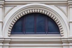 在白色石古老大厦门面的一个半圆窗口与被雕刻的装饰的 图库摄影