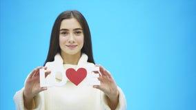 在白色衣裳打扮的年轻俏丽的女孩 在这时间它在蓝色背景站立 举行爱的词  影视素材