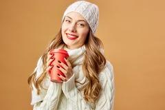 在白色被编织的毛线衣和帽子打扮的微笑的女孩在演播室在她的手上拿着一个红色杯子在米黄背景 免版税图库摄影