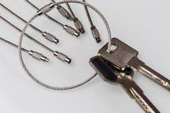 在白色背景是在链子的钥匙 其他链子设法带领 欺骗的概念在不动产的 库存图片
