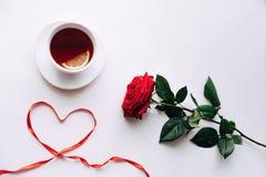 在白色背景的红色玫瑰,丝带在ide的心脏在3月8日前 图库摄影