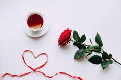 在白色背景的红色玫瑰,丝带在ide的心脏在3月8日前 免版税库存照片