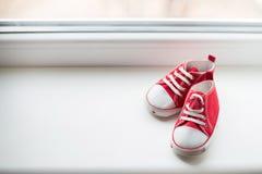 在白色背景的逗人喜爱的红色小型帆布鞋顶视图与copyspace 免版税库存照片
