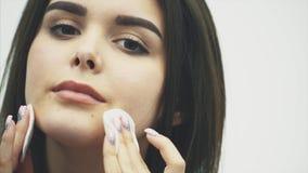 在白色背景隔绝的一个可爱的年轻白种人微笑的深色的女孩的特写镜头画象 清洗她的面孔 影视素材