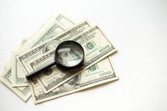 在白色背景隔绝的美国美元的放大镜谎言 库存照片