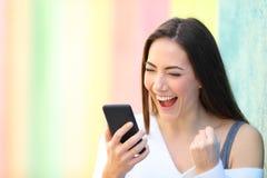在电话的激动的女孩读书喜讯在一条五颜六色的街道 免版税库存图片