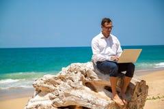 在衬衣的愉快的商人有膝上型计算机的和有玻璃的走在海滩的 免版税库存图片