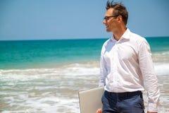 在衬衣的愉快的商人有膝上型计算机的和有玻璃的走在海滩的 图库摄影