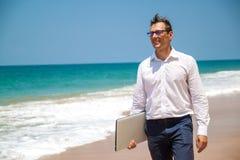 在衬衣的愉快的商人有膝上型计算机的和有玻璃的走在海滩的 免版税库存照片