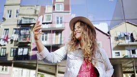 在街道上的妇女观看的智能手机在玻璃墙附近 股票视频