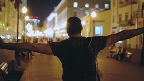 在街道夜城市下的人步行和涂他的胳膊为生活自由支持 股票录像