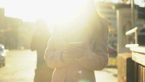 在被日光照射了街道上的年轻女性拜访的智能手机身分,分享情感 股票视频