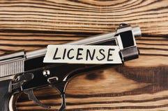 在被撕毁的纸和光滑的手枪的题字执照 免版税库存照片