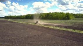 在被耕的领域的空中行动对反对森林的拖拉机 股票视频