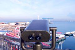 在观察台的大双筒望远镜反对海港 免版税库存照片