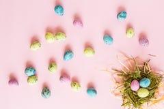 在说谎在桃红色纸背景的巢和花卉分支的被绘的鸡蛋 复活节装饰 平的位置 顶视图 图库摄影