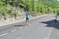 在路的女孩奔跑在山 免版税库存照片