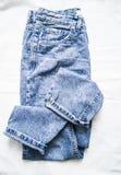 在轻的背景,顶视图的蓝色退色的妈妈牛仔裤 时装 免版税图库摄影