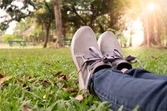 在运动鞋的妇女脚在绿草在公园 免版税库存图片