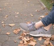 在运动鞋的妇女脚在绿草在公园 库存图片