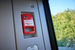 在近红色紧急制动器把柄的抽象看法对在新的现代欧洲客车的自动门 乘客和trai 免版税库存图片