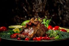 在蜂蜜烤用BBQ调味汁和变成焦糖的排骨特写镜头  鲜美快餐供食与在板材的绿色幼木 图库摄影