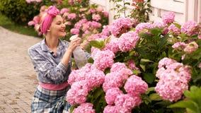 在花的美丽的卖花人妇女浪花 喷洒在开花的花植物的愉快的年轻女人液体肥料 花 股票录像